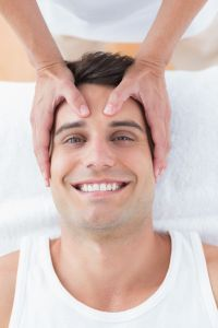 38353526 - smiling man receiving head massage in medical office
