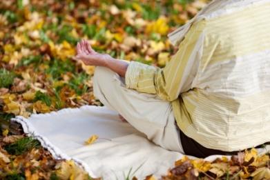 21246789 - rear view of senior woman meditating in lotus position at park